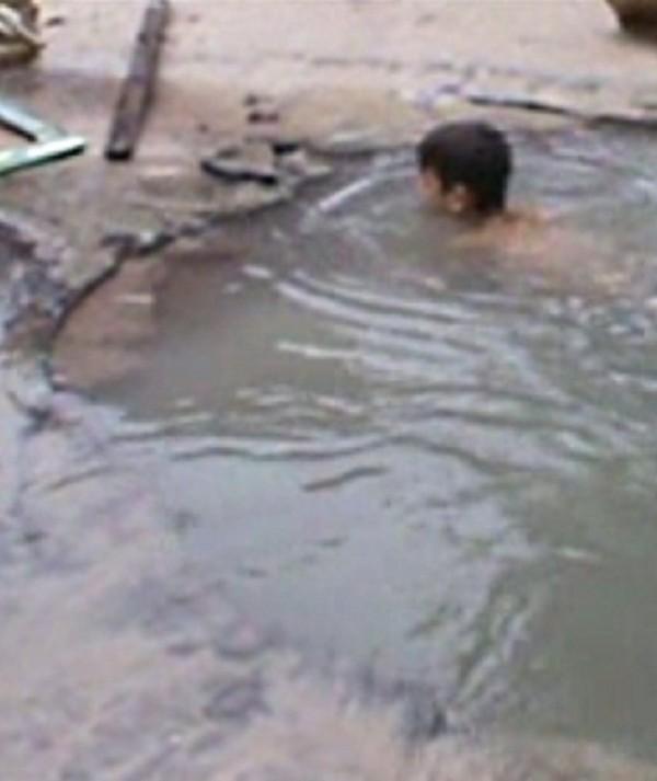 Moradores transformam cratera no asfalto em piscina em Fortaleza